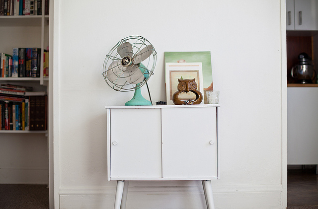 Blue vintage fan on white table.
