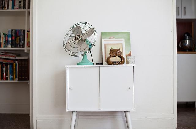 Blue vintage fan on white table.