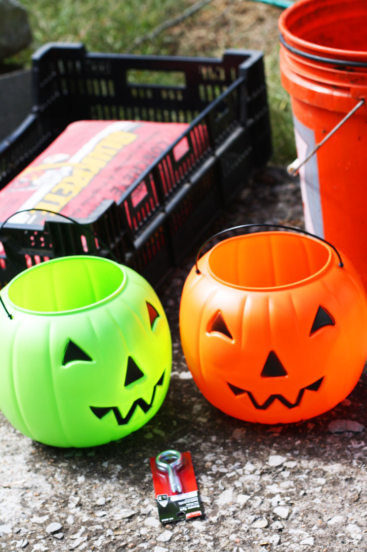 Plastic pumpkin buckets and concrete are the mixture for the ultimate DIY concrete jack-o-lantern. | redleafstyle.com